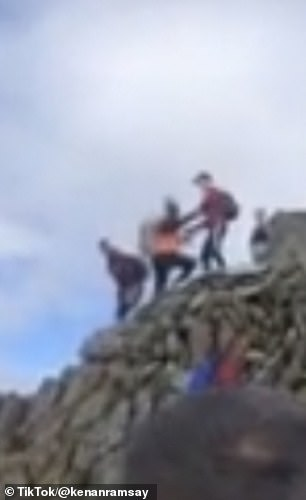As the man reaches the concrete trig point, he appears to clash with another hiker, who appears to block his way to the top.