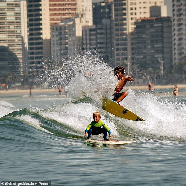 The brave youngster is seemingly unfazed by the waves and flexs his impressive skills in the water every single day, sometimes joined by other bigger surfers