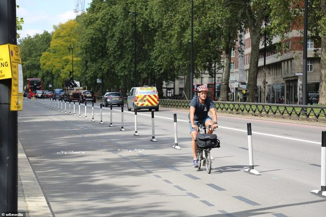A lone cyclist travels along a bike lane on Park Lane in London's exclusive Mayfair district at 2.30pm yesterday