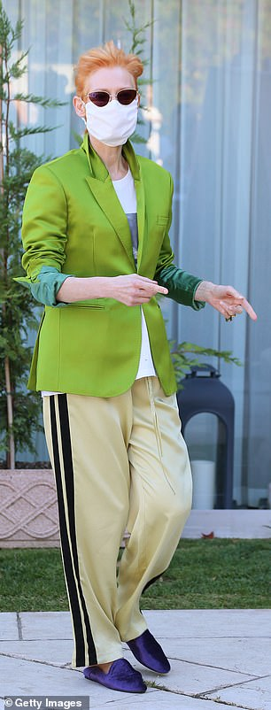 Stunning: Tilda kept her face mask as she posed for photos outside the chic hotel