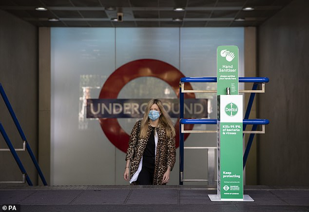 A woman walks up the steps next to a hand sanitising unit at London Kings Cross this morning