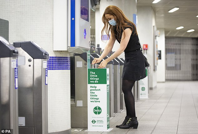 A woman uses a hand sanitising unit at London Kings Cross Underground station this morning