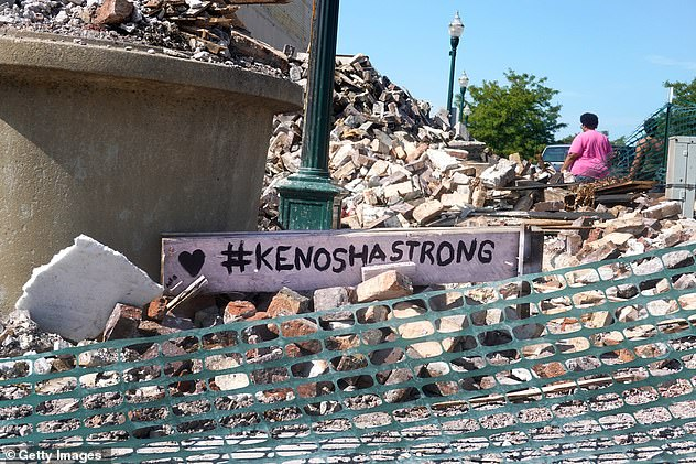 A sign with the phrase '#KenoshaStrong' is seen among the rubble of a building that was burned down during riots that erupted after Blake was shot