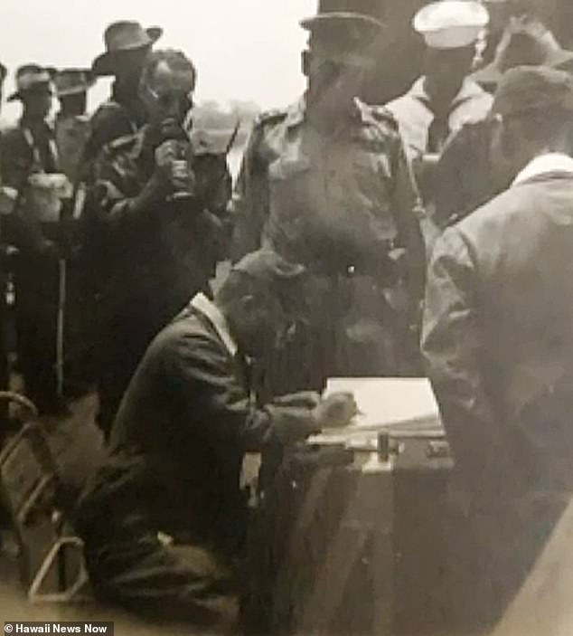 The son of a World War II veteran on Wednesday released images secretly taken at a Japanese surrender ceremony on September 11, 1945. This image shows an officer signing papers on an Australian ship
