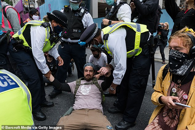 A protester is pulled up from the ground by police in London after attempting to block a road during protests this morning