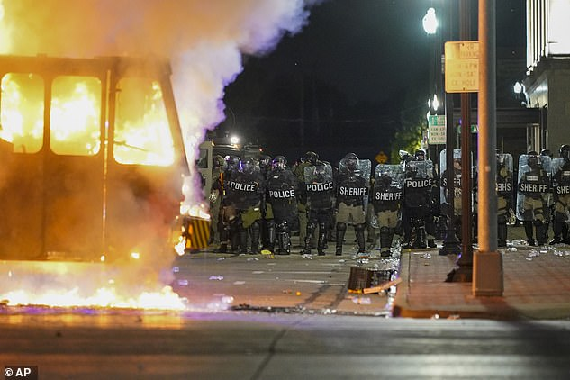 Police stand near a garbage truck ablaze on August 24 during protests over the shooting of Jacob Blake in Kenosha