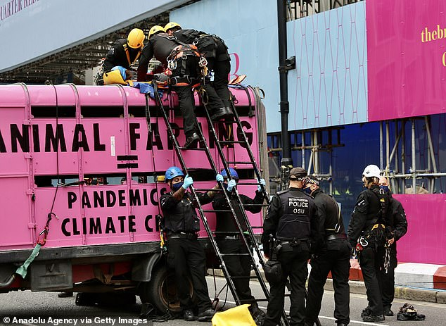 Extinction Rebellion protesters chain themselves inside and over the van and block the road to draw attention on animal rights in London on September 3, 2020
