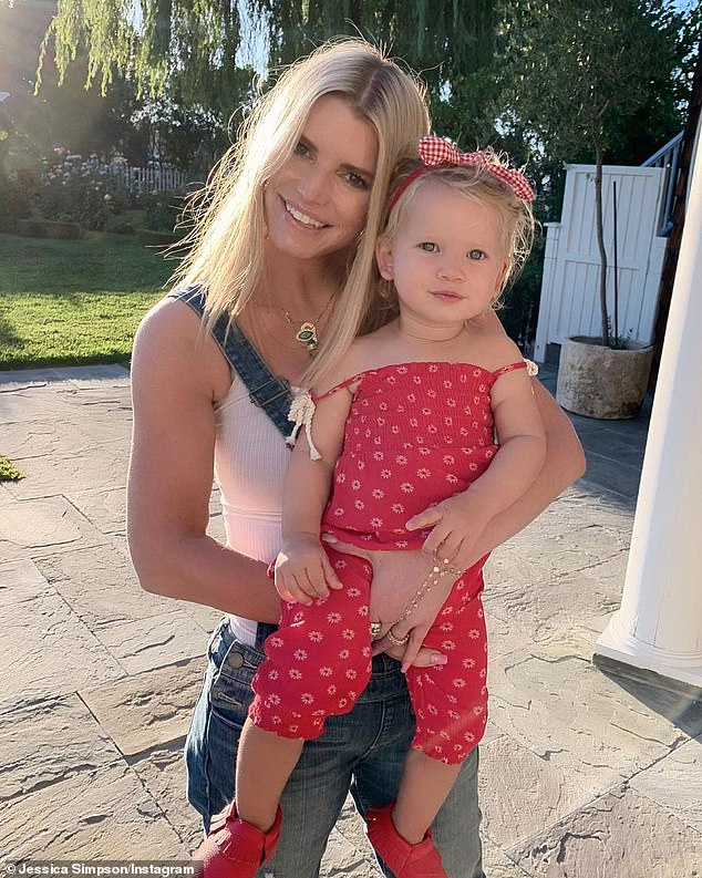 She loves her jeans! Simpson is seen with her youngest child Birdie; she has on denim overalls