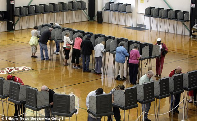 State election officials are expecting a larger share of voters to cast their ballots by mail this year rather than go to the polls like these voters in Cary, North Carolina in 2012