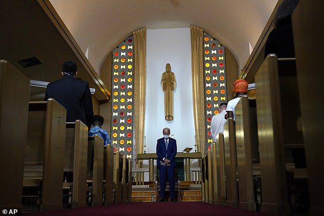 Joe Biden bows his head in prayer at theGrace Lutheran Church in Kenosha, Wisconsin where he held a listening session with community leaders Thursday, two days after President Donald Trump visited the city