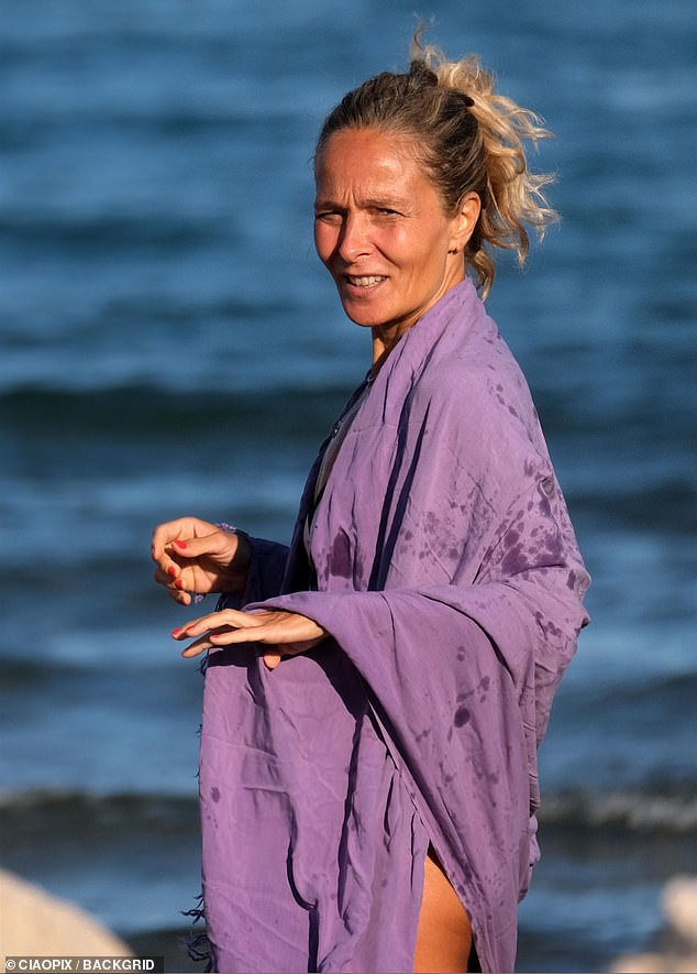 Casual: his mate wrapped in a purple kaftan after emerging from the ocean