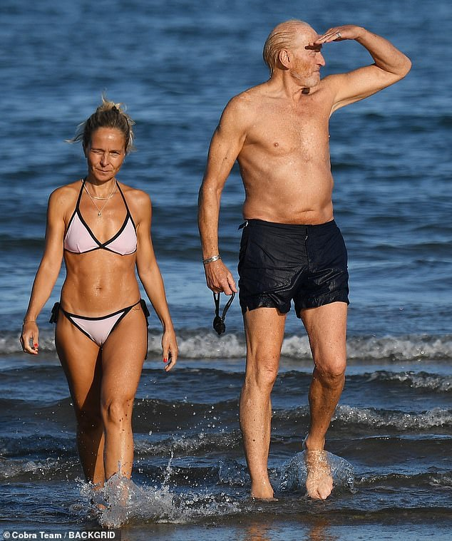 Lovely: He was soon joined by his girlfriend, who opted for a pale pink bikini with black stripes