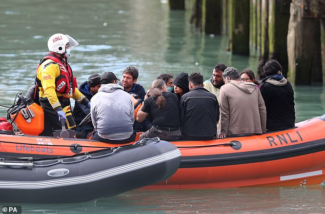 Eight in ten migrants who reach Britain in small boats are refused asylum, Home Office chiefs revealed yesterday (pictured, RNLI boat brings people thought to be migrants into Dover)