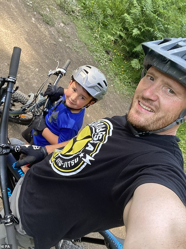 Jonathan Lake with his son. The Welsh father-of-two whose family will have to self-isolate for 14 days after remaining out in Greece has branded the inconsistency between Westminster and Cardiff 'an absolute joke'