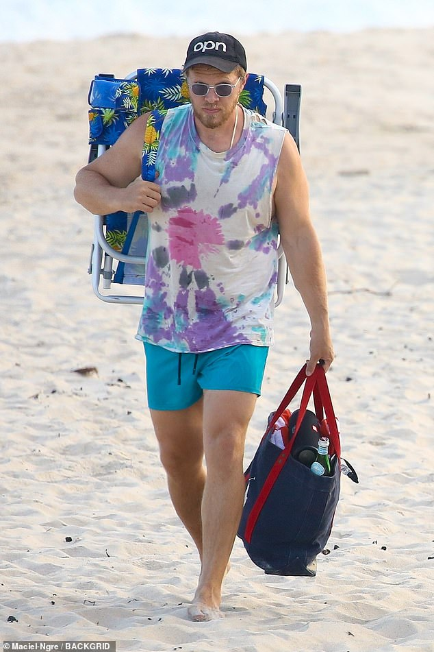 Gentleman:The acclaimed film producer had an OPN hat on his head and a pair of shades over his eyes as he held onto their overstuffed beach bag