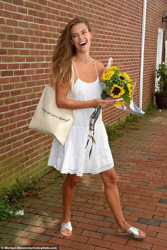 Sunflowers: The fashion model also carried a large bouquet of sunflowers as she exited the shop