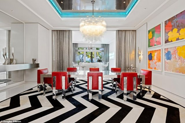 Florida estate: The formal dining room has a floor of black-and-white marble chevron patterns upon which sits a silver dining table with bright red chairs. There's a stunning chandelier and walls covered in Andy Warhol flower prints