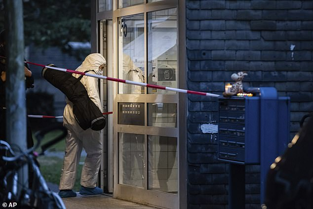 A female forensic investigator enters the apartment building where five children were found dead in Solingen on Thursday