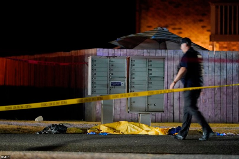 What appears to be a body is seen as officers work the scene of the fatal confrontation