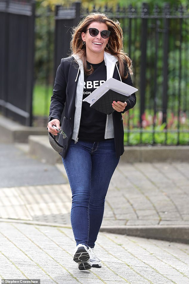 Amused: Coleen Rooney made a cheerful display as she left her Cheshire living room on Friday ... after finding Rebekah Vardy's 'tactic to speed up the £ 1million trial laughable'
