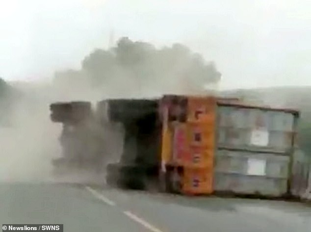 The lorry eventually completely falls over, narrowly avoiding the motorcyclists and comes to a crashing stop, launching a cloud of dust into the air