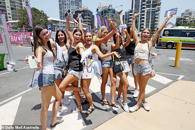 A group of girls pose on Cavill Avenue in Surfers Paradise before a Schoolies event in 2019