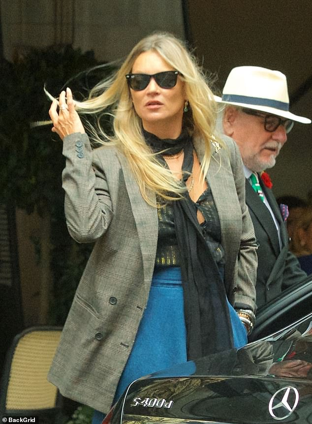 Radiant: The supermodel, 46, looked dazzling in a pussy-bow blouse tucked into a high-waisted blue skirt and worn under a chic gray blazer