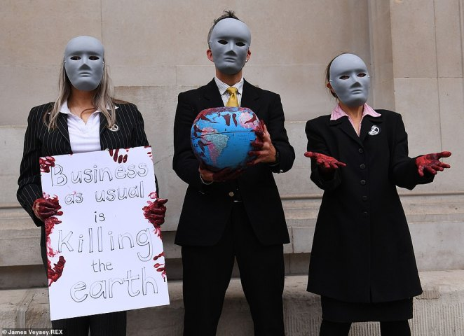 Masked Extinction Rebellion protesters outside the Bank of England holding a globe containing fake blood and signs that say 'business as usual is killing the earth'