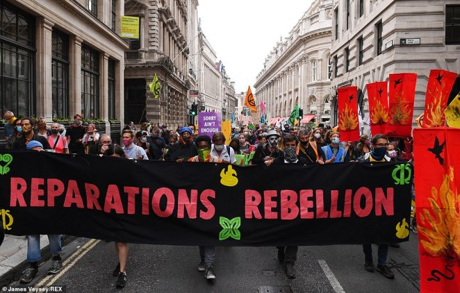A protest in Bank, London, with people wearing face coverings and holding a 'reparations rebellion' banner