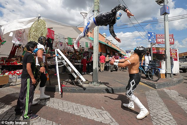 Lucha libre wrestlers Ciclónico, Gran Felipe Jr. and Rey Optium take part in an impromptu match while they took a break in handing out face masks to residents while visiting the Mexico City borough of Xochimilco to spread awareness about the COVID-19 epidemic