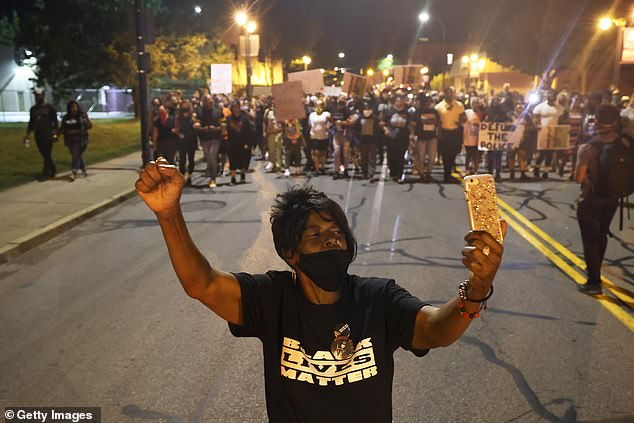 A woman records a live video during Thursday night's protest in Rochester