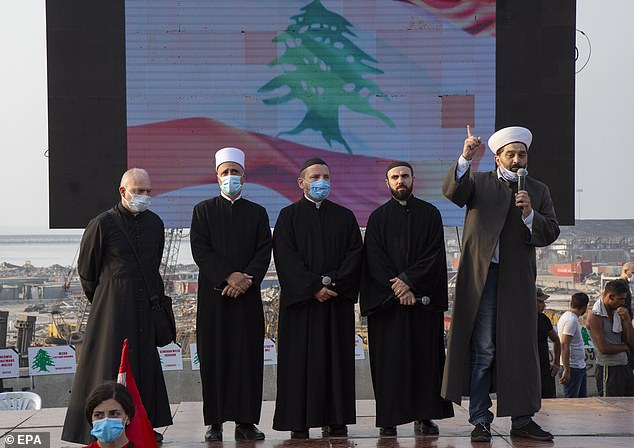 Christian and Muslim clerics speak as families of Beirut port explosion victims and anti- government protesters gather during a minute of silence and prayer