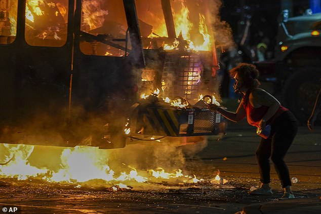 Karmo and Smith told authorities they had traveled to Kenosha to see evidence of the protests themselves. A protester is shown lighting a cigarette on a garbage truck set on fire August 25