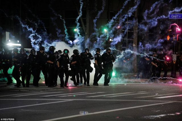 Flares go off in front of police officers during a protest over the death of a Black man, Daniel Prude, after police put a spit hood over his head during an arrest on March 23