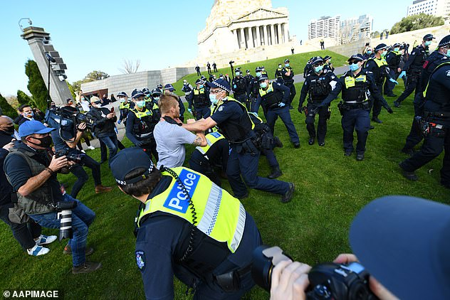One man is seen caught in a scuffle with a Victorian police officer during the protest (pictured on Saturday) with wild scenes caught on camera