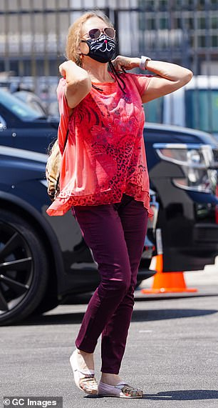 All eyes on her: Carole took a walk on the wild side as she teamed a red leopard print T-shirt with velour trousers