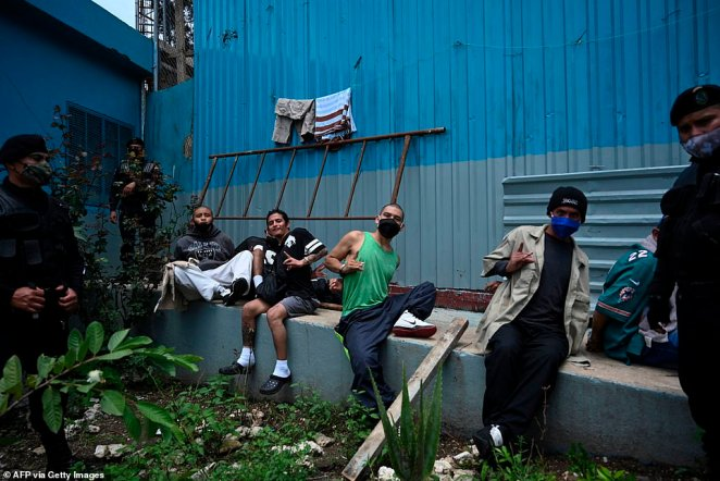 Police stand guard next to Mara 18 gang members at a prison in Guatemala City yesterday