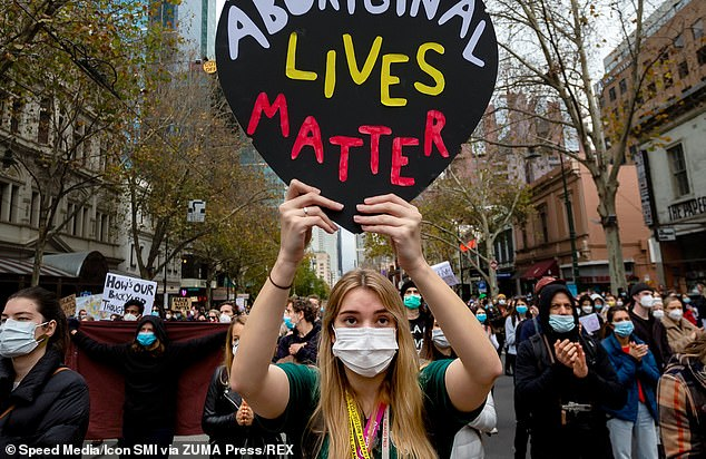 Masked protesters holding placards march through the CBD during a Black Lives Matter rally Black Lives Matter Rally on June 6