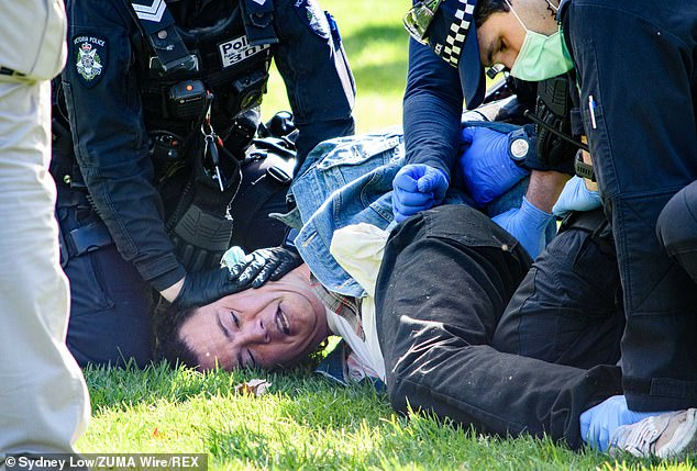 A protester is arrested at a Freedom Day protest against lockdown regulations in Melbourne