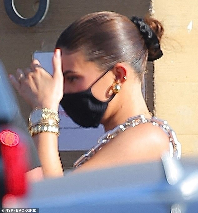 Slick: The Kylie Cosmetics founder had her hair styled into a slick bun and she rocked a black cloth face mask