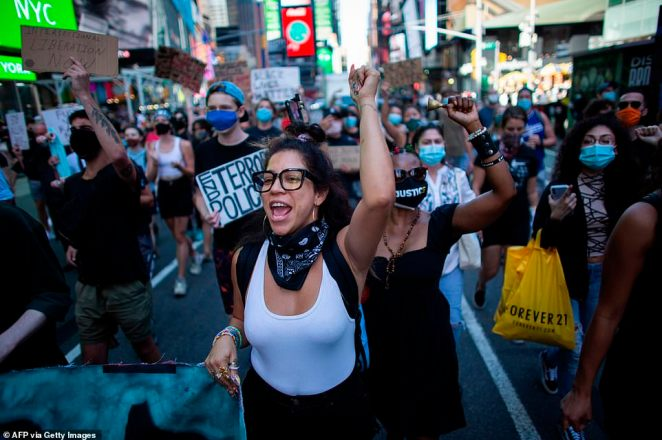 Activists raised their fists as they marched through Times Square on Saturday, calling for an end to police brutality