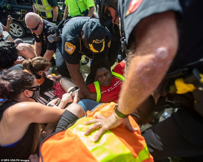Law enforcement officers take several Black Lives Matter protesters into custody during a peaceful march on Saturday after a confrontation between a woman and law enforcement