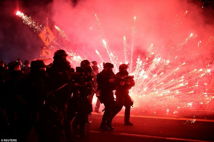 Police advance on protesters as fireworks are deployed to clear a street on the 100th consecutive night of protests against police violence and racial inequality