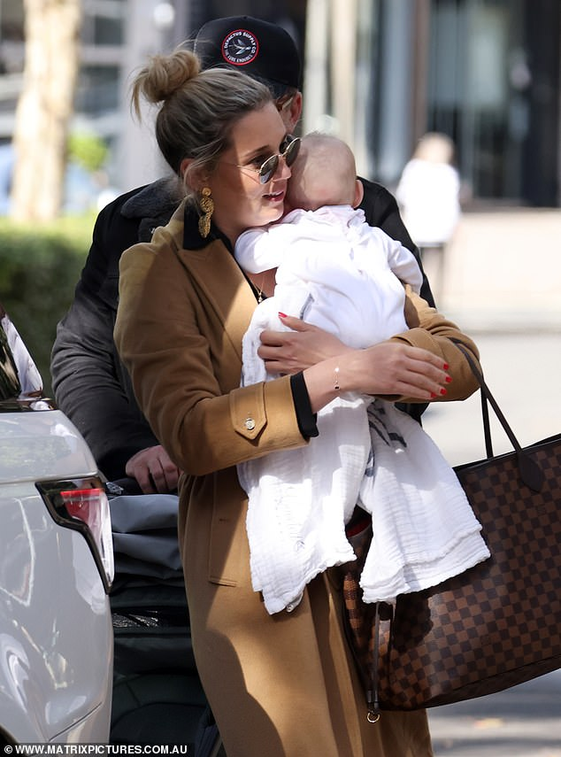 Attentive: Jasmine, who cut a chic figure in a black blouse, leather-look pants, mules and a tan trench coat, cradled adorable Harper