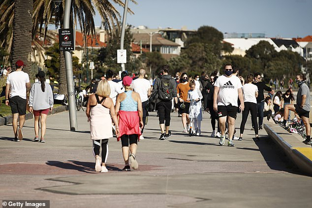 Melbourne residents take to the board walk at St Kilda Beach for their daily hour of exercise on Sunday