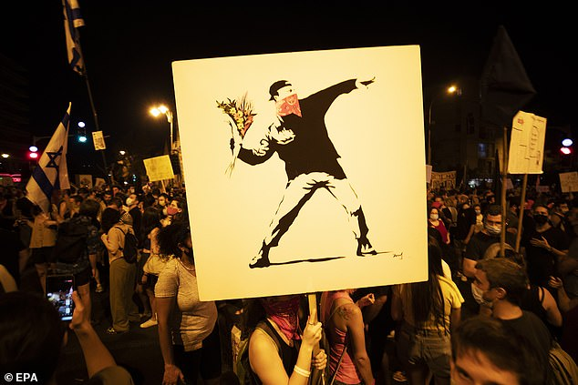 An Israeli protester holds a Banksy painting during the Saturday protest against Netanyahu