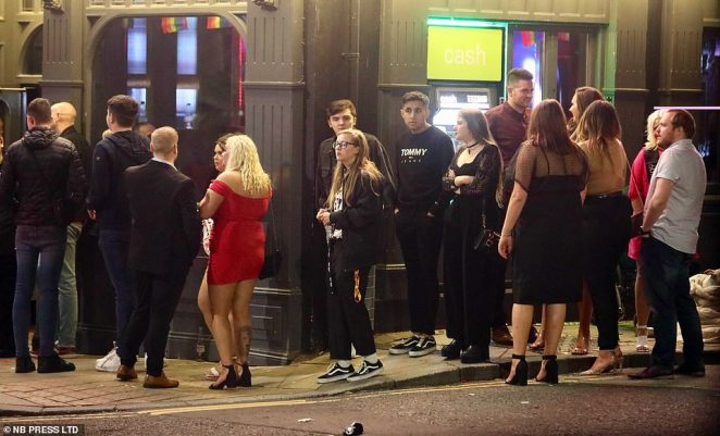 Revellers flout social distancing guidelines as they stand outside a pub despite the city teetering on the brink of a local lockdown