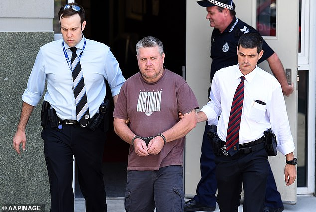 Pictured:Rick Thorburn is escorted by officers from the Logan Central Police Station in September 2016