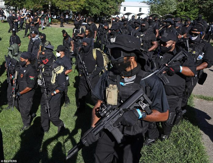 Members of a black militia group NFAC march in protest over the police killing of Breonna Taylor in Louisville