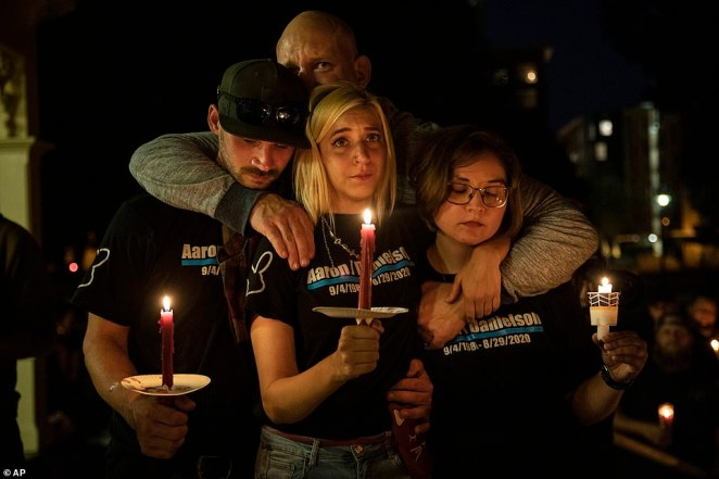 "Mack Lewis (left)  Haley Adams (center) Emma Mitchem (right) and Nate Millsap (rear) comfort each other during a candlelight vigil Saturday in Vancouver, Wash., for Aaron ""Jay"" Danielson, a supporter of Patriot Prayer"